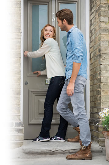 happy couple opening their front door